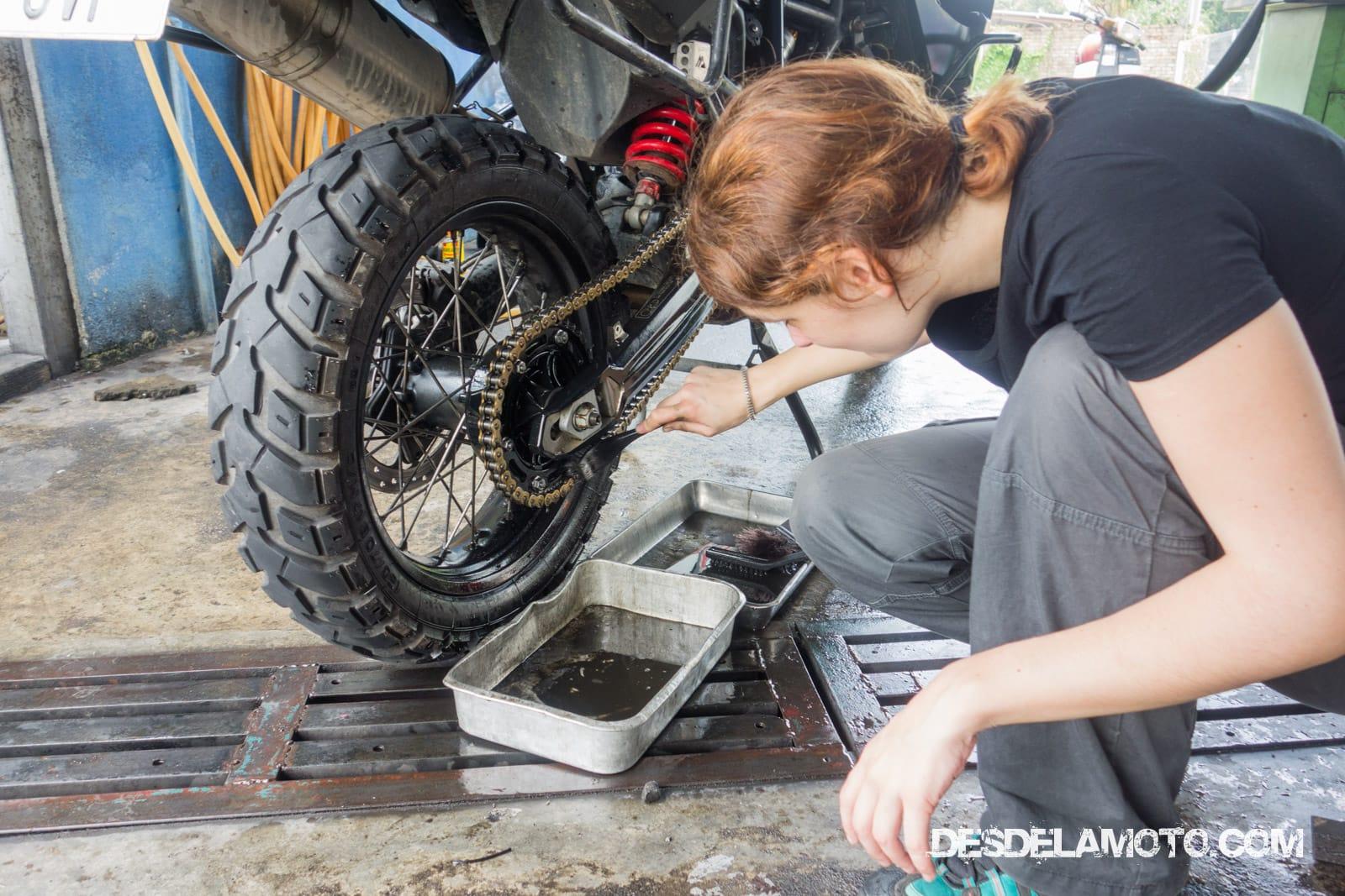 Diana limpiando la cadena de la moto.